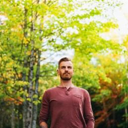 Graeme Stewart-Robertson, artist, in a wooded area looking forward