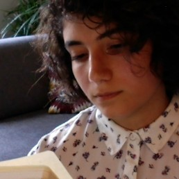 Artist Nazanin Oghanian glancing down to read a book